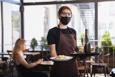 Serveuse d'un restaurant portant un masque